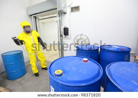 Fully protected in yellow uniform,mask,and gloves professional dealing with barrels with toxic wastes - stock photo