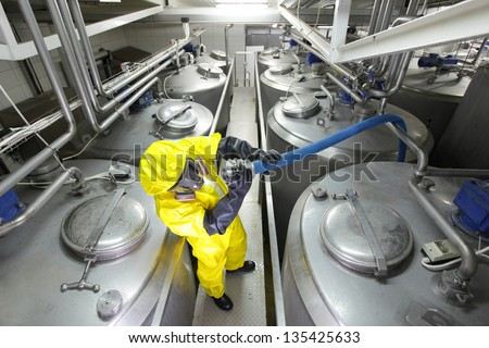 fully protected in yellow uniform,mask,and gloves technician  checking large process hose in factory