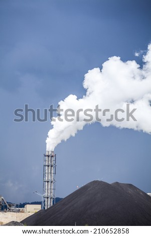 Fuming chimney of a factory against stormy sky. - stock photo