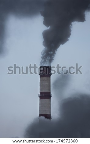 Fuming tube pollutes the atmosphere, outdoors shot, industrial building - stock photo