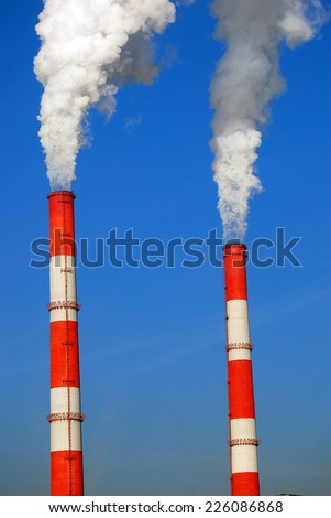 Fuming tubes. Blue sky background. - stock photo
