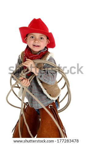 fun adorable young cowboy playing with rope