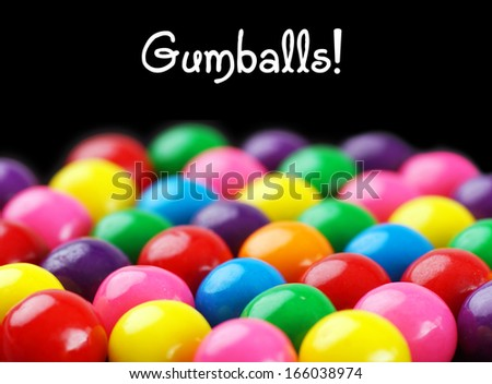 Fun and colorful gumballs on black background with text - stock photo