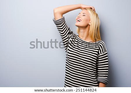 Fun and flirty. Beautiful young blond hair woman keeping hand in hair and smiling while standing against grey background   - stock photo