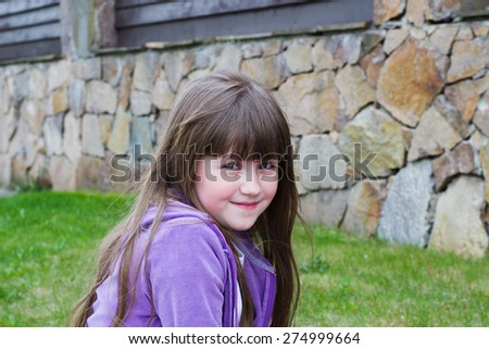 fun and funny little girl close-up in blue jacket outdoors