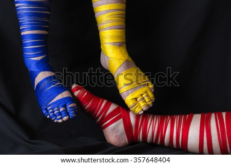 Fun and playful, these feet were wrapped in yarn in the primary colors and on black this makes a stunning photo in a horizontal format and great for imaginative ideas and concepts. - stock photo