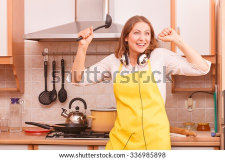 Fun and relax. Cooking and preparing meal in house kitchen. Funny cute housewife woman wearing earphones dancing with spoon ladle. Indoor.