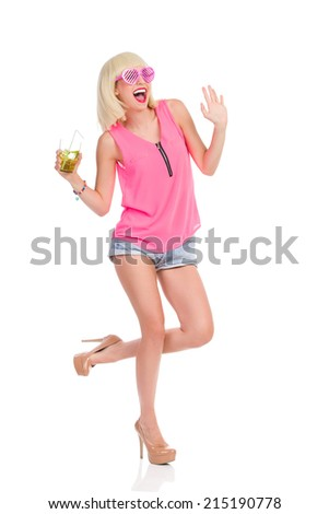 Fun at the party. Carefree blonde young woman in high heels, pink top and jeans shorts dancing with lime drink and waving hand. Full length studio shot isolated on white. - stock photo