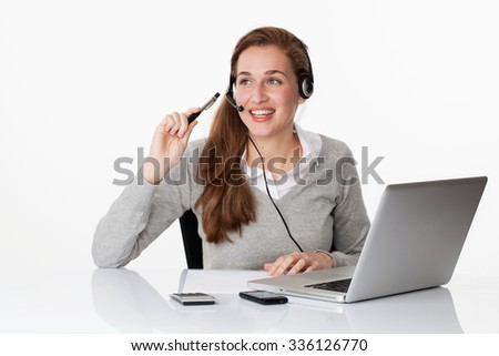 fun at work concept - smiling young female business executive thinking on headset with computer on sparse desk, studio shot,white background - stock photo