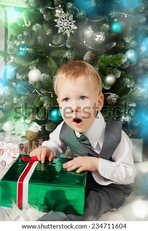 Fun baby near present gift box while Christmas time - stock photo
