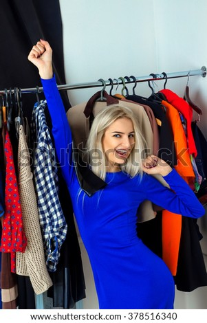 Fun beautiful blonde woman chooses clothes in shop. Happy young lady with a lot of clothes. Shopping concept. - stock photo