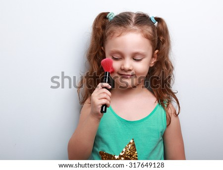 Fun beautiful small kid girl applying tonal cosmetic on the face using makeup brush with happy smile on blue background - stock photo