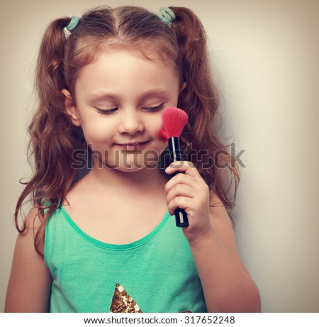 Fun beautiful small kid girl applying tonal cosmetic on the face using makeup brush with happy smile. Closeup portrait - stock photo