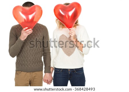 Fun being together. Studio shot of a loving couple holding hands hiding their faces behind red heart shaped balloons