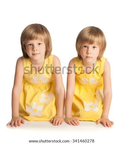 Fun blonde girls in yellow dresses on the floor crawling on my knees-Isolated on white background - stock photo