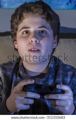 Fun boy with joystick playing computer game at home.
