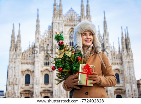 Fun Christmas trip to Milan, Italy. happy modern traveller woman in the front of Duomo in Milan, Italy with Christmas tree and gift looking into the distance