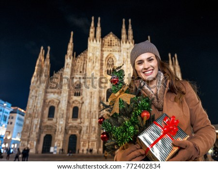 Fun Christmas trip to Milan, Italy. Portrait of smiling modern woman with Christmas tree and gift in Milan, Italy