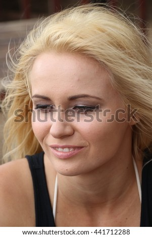 Fun closeup portrait of long haired blond lovely sweet model with hair blowing in wind