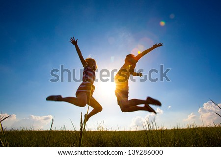 Fun couple in jump on the outdoor background - stock photo
