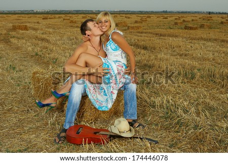 fun  couple of lovers on hay with guitar in summer at sunset. - stock photo
