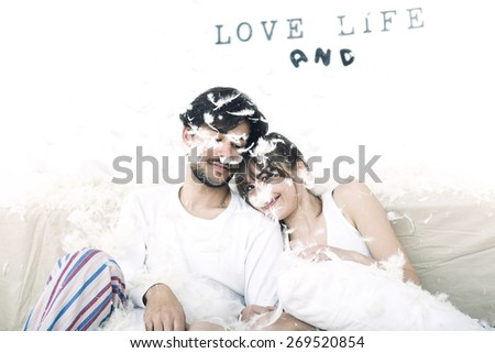 Fun couple resting affectionately after a pillow fight - stock photo