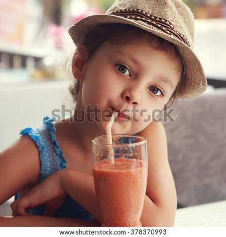Fun cute kid girl drinking healthy smoothie juice in street restaurant. Closeup toned portrait