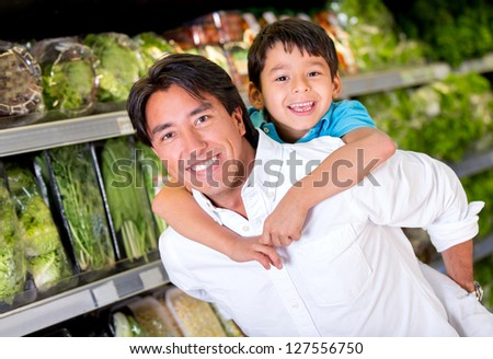Fun dad carrying children at the supermarket - stock photo