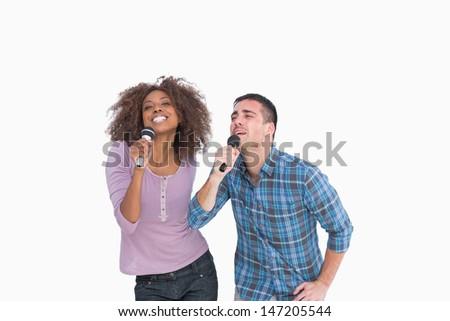 Fun duo singing at karaoke on white background - stock photo