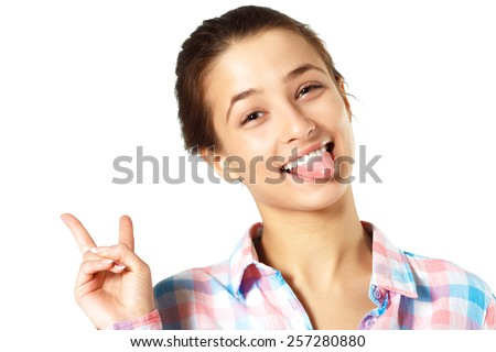 Fun Emotion Girl Sticking Out Tongue And Victory Gesture. Bright Studio Photoshoot - stock photo