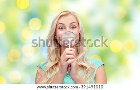fun, emotions, expressions and people concept - happy smiling young woman or teenage girl having fun with magnifying glass over summer green lights background - stock photo