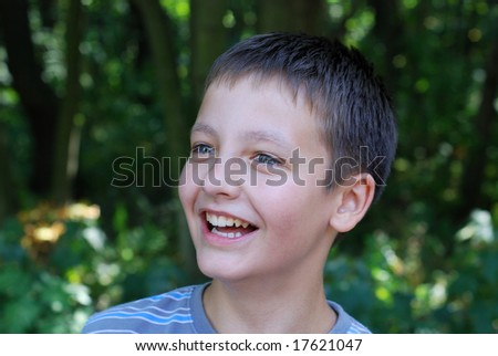 Fun face of light boy with wide smile and shiny eyes in the dark green background, closeup