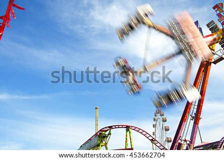 Fun fair amusement festival park attractions swinging up with motion blur against a blue sky on a sunny day, outdoor activities. Bright ferris wheel and roller coaster rides with lights, exterior. - stock photo