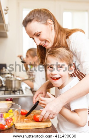 Fun family cooking. Son with mother cut tomatoes in the kitchen and have fun of eating