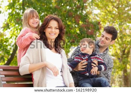 Fun family portrait at the park. Shallow focus. - stock photo