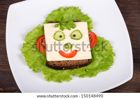 Fun food for kids - face on bread, made from cheese, lettuce, tomato, cucumber and pepper. - stock photo