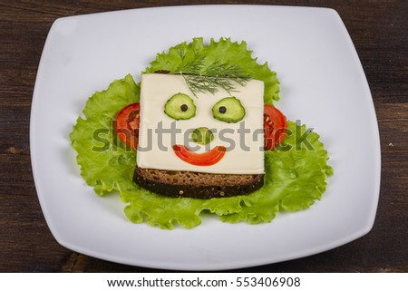 Fun food for kids - face on bread, made from cheese, lettuce, tomato, cucumber and pepper. Close up