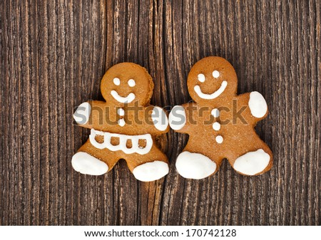 Fun Gingerbread couple on vintage wooden surface top view background  - stock photo
