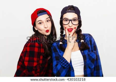 Fun girl stick tongue out between two fingers showing cunnilingus sign. Colorful comic funny emotional hipster summer style twins teenager girls make faces and have fun. Isolated on a grey background. - stock photo