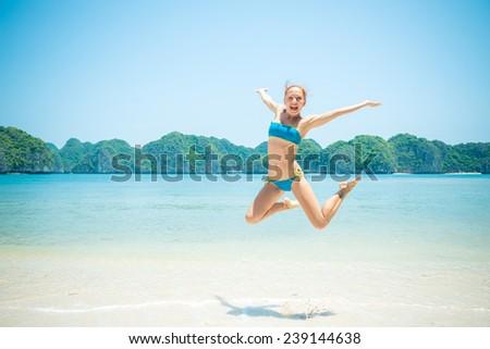 Fun girl wearing bikini jumping on a beach - stock photo