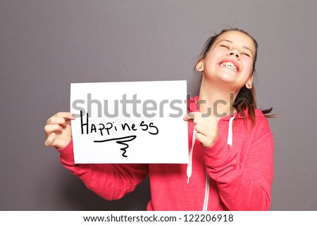 Fun Happiness concept with a young girl holding up a handwritten sign saying Happiness and tilting her head back with a cheeky ear to ear grin - stock photo