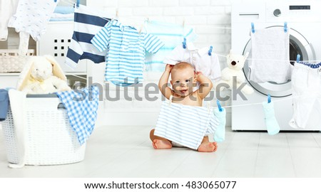 fun happy baby boy  to wash clothes and laughs in the laundry room