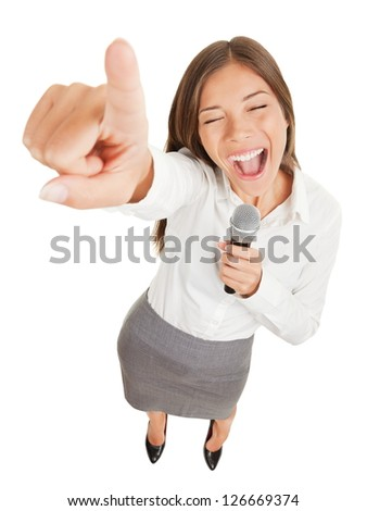 Fun high angle view of a passionate attractive young woman holding a microphone singing or making a point during a speech gesturing and pointing her finger at the camera isolated on white - stock photo