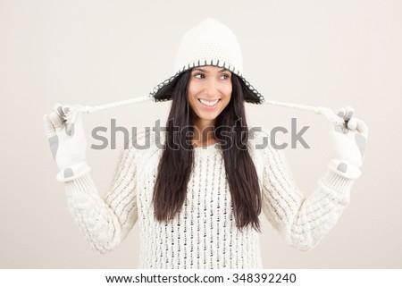 Fun hip woman holding her beanie starps - stock photo