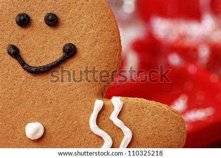 Fun holiday image of smiling gingerbread man with red and white defocused background (christmas dishes with candy)  Macro with extremely shallow dof. - stock photo