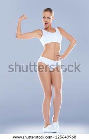 Fun image of a shapely athletic woman in skimpy sportswear displaying her biceps which are unforunately rather underdeveloped - stock photo
