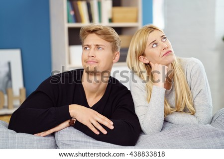 Fun image of a thoughtful young couple leaning over the back of a sofa together looking up in opposite directions with quirky pensive expressions - stock photo