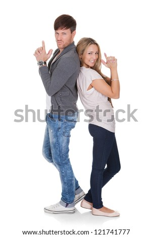 Fun image of a young attractive dueling couple standing back to back with their hands raised on a white background