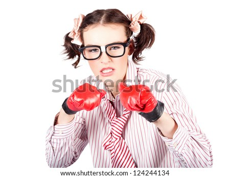 Fun image of a young woman in nerdy glasses and pigtails gritting her teeth in determination or aggression wearing a pair of red boxing gloves and holding her fists in the defensive position - stock photo