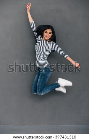 Fun in midair. Beautiful young cheerful Asian woman looking at camera with smile while jumping against grey background - stock photo